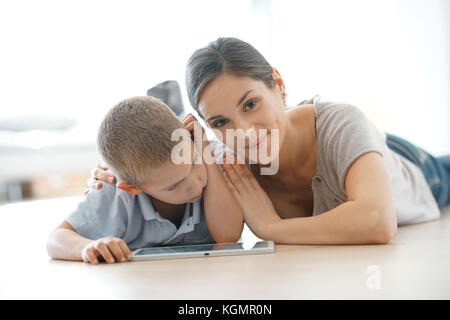 Mommy with little boy playing with digital tablet - Stock Photo