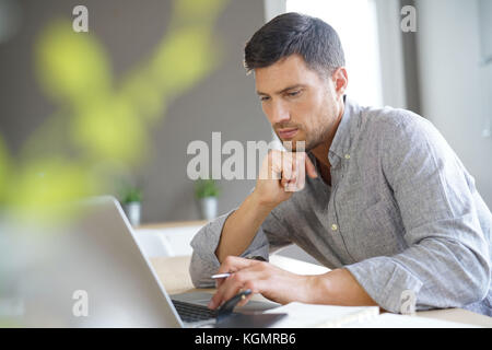 Middle-aged man working from home on laptop computer - Stock Photo