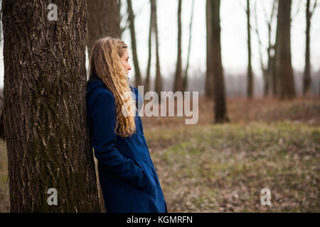 Lonely woman standing in forest in winter - Stock Photo