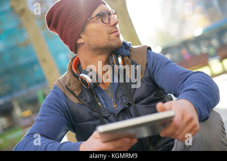 Hipster guy in the street websurfing on tablet - Stock Photo