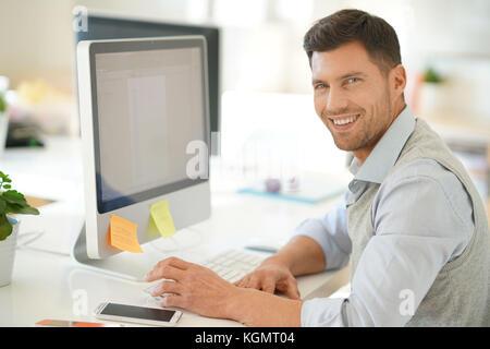 Handsome businessman working on desktop computer in office - Stock Photo