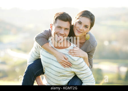 Portrait of cheerful man giving piggyback ride to girlfriend - Stock Photo