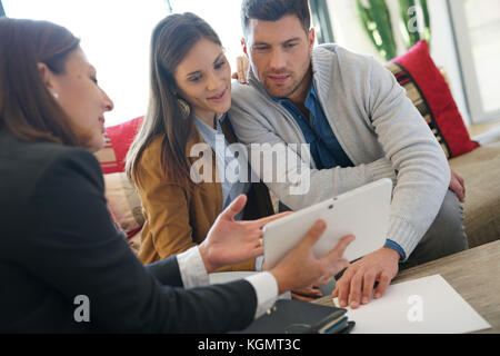 Real estate agent showing house project on tablet to clients - Stock Photo
