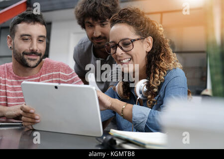Young entrepreneurs working on digital tablet - Stock Photo