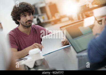Young entrepreneur man working in office on laptop - Stock Photo