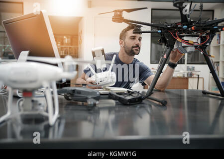 Engineer working on drone in office - Stock Photo