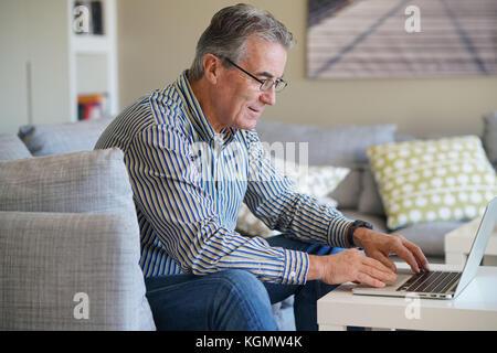 Senior man in living-room using laptop computer - Stock Photo