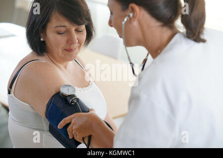 Mature woman at the doctor, controlling blood pressure - Stock Photo
