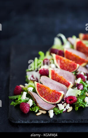 Delicious salad with fresh figs, raspberry and duck meat on dark background - Stock Photo