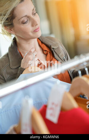 Middle-aged woman shopping in clothing store during sales season