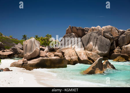 The Seychelles, La Digue, Anse Cocos, beach, eroded granite rock formation in sea - Stock Photo