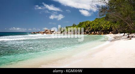 The Seychelles, La Digue, Anse Cocos, tourists sunbathing on idyllic tropical beach - Stock Photo
