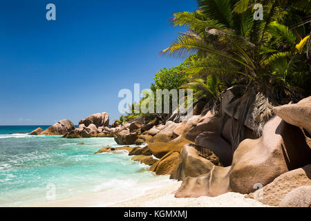 The Seychelles, La Digue, Petit Anse, beach, eroded granite rock formation in sea - Stock Photo