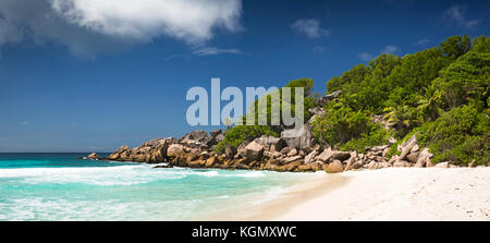 The Seychelles, La Digue, Petit Anse, beach, eroded granite rock formation in sea , panoramic - Stock Photo