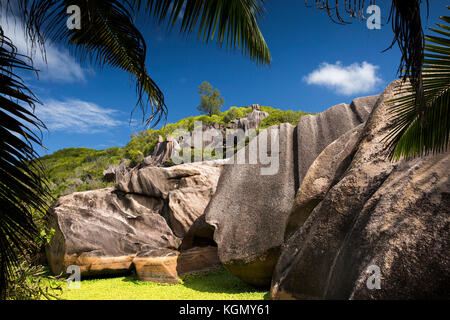 The Seychelles, La Digue, Grand Anse, eroded granite rock formation on hill behind beach - Stock Photo