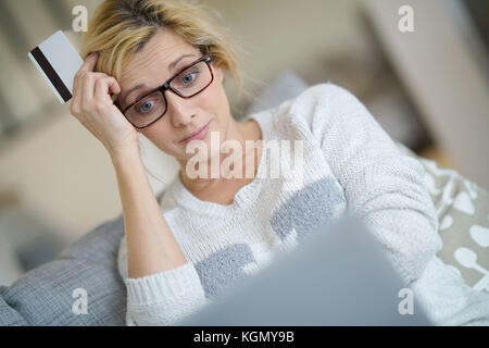 Middle-aged woman at home buying on internet with credit card - Stock Photo