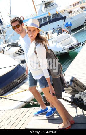 Happy couple getting on board for sailboat cruising - Stock Photo