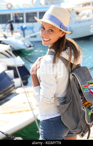 Cheerful girl getting on boat for adventure - Stock Photo