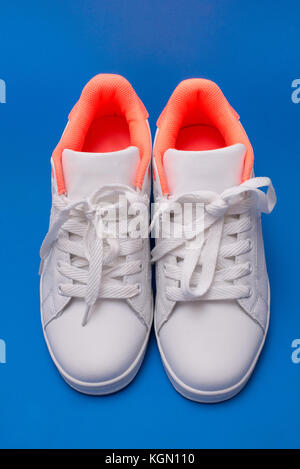 Pair of white sneakers isolated on blue background. Sport shoes - Stock Photo