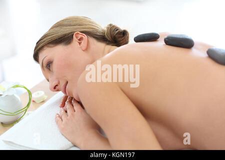 Woman in beauty salon having hot stones massage - Stock Photo
