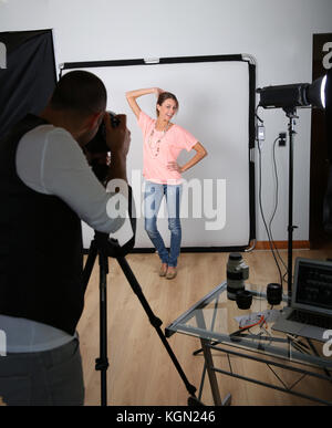 Photographer shooting model in studio - Stock Photo