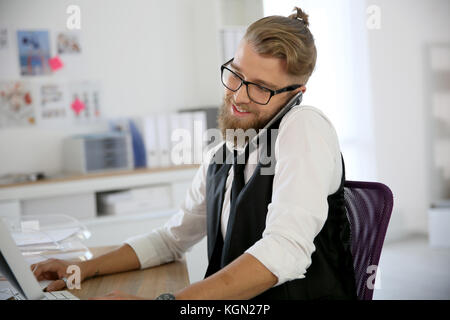 Young designer in office talking on phone - Stock Photo