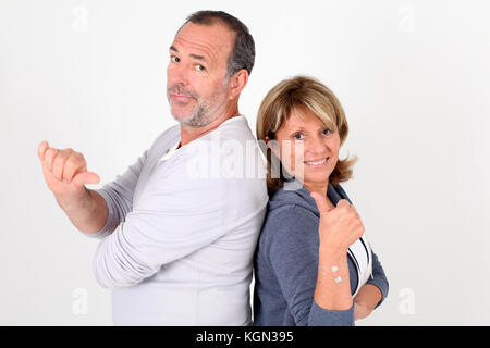 Senior couple with thumbs up and down - Stock Photo