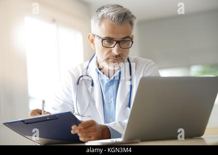 Doctor in office working on patient file - Stock Photo