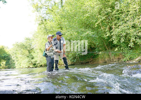 Father and son fly-fishing in river - Stock Photo