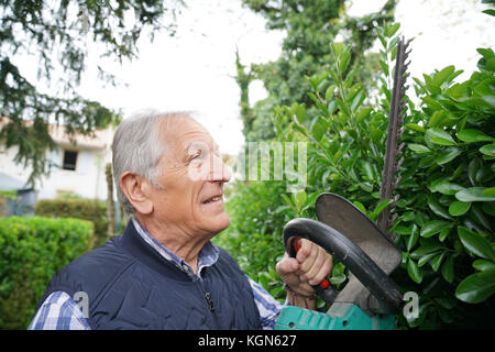 Senior man using hedge trimmer - Stock Photo