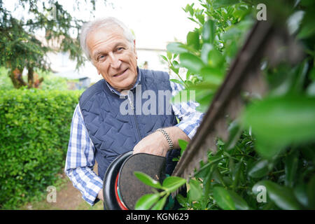 Senior man using hedge trimmer - Stock Photo