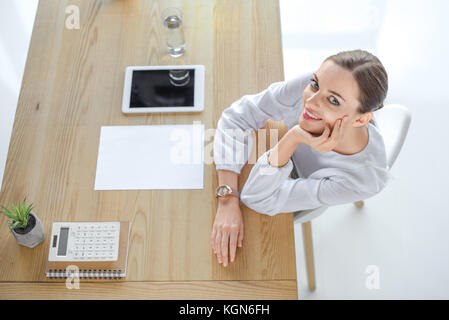 Smiling businesswoman at desk in office - Stock Photo