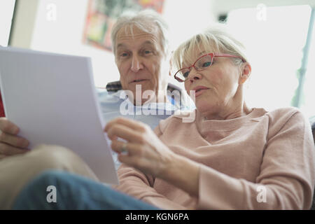 Senior couple in sofa reading official documents - Stock Photo