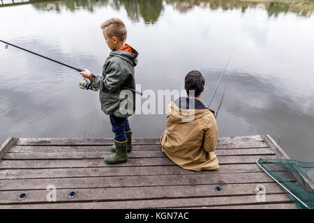 father and son fishing with rods - Stock Photo