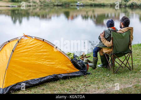 father and son sitting at tent - Stock Photo