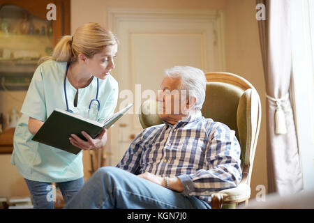 Nurse checking senior male patient results - Stock Photo