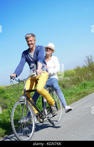 Cheerful couple riding bike on a sunny day - Stock Photo