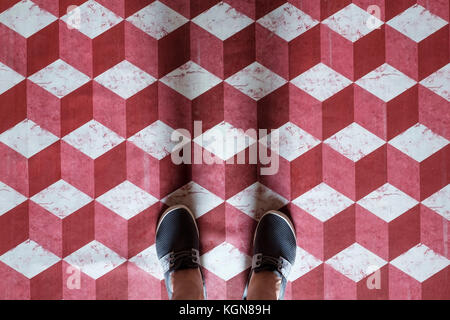 Selfie of feet with sneaker shoes on art pattern tiles floor red and white 3d cube - Stock Photo