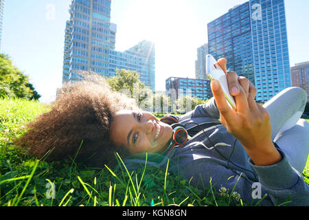 Portrait of mixed race girl laying in park using smartphone - Stock Photo
