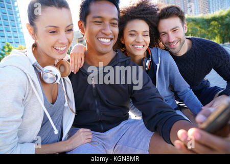 Group of friends in casual outfit taking selfie picture with smartphone - Stock Photo
