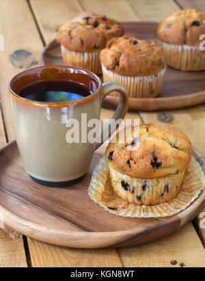 Blueberry muffin and cup of coffee on a wooden plate - Stock Photo