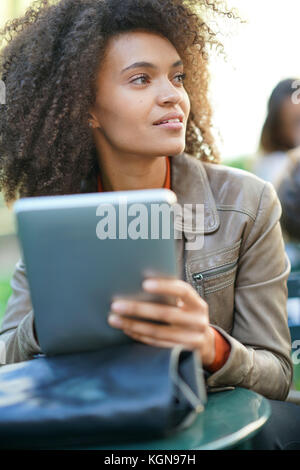 Businesswoman sitting in park, working on digital tablet - Stock Photo