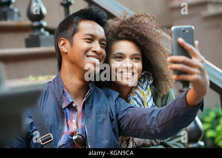 Mixed-race couple taking selfie picture - Stock Photo