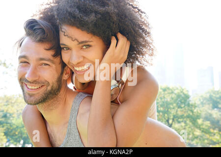 Man giving piggyback ride to woman at Central Park - Stock Photo