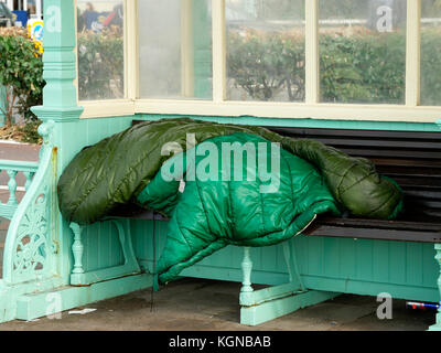 Homeless person sleeping rough in seafront shelter Brighton England - Stock Photo