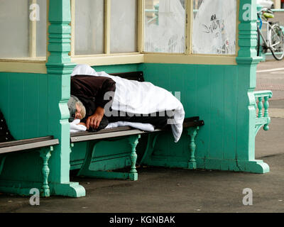 Homeless  person sleeping rough in seafront shelters Brighton England - Stock Photo