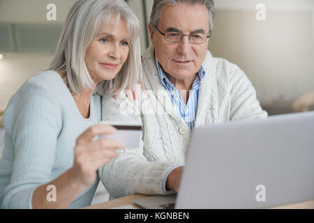 Senior couple buying on internet with credit card - Stock Photo
