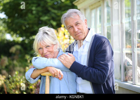 Senior couple standing by greenhouse in garden - Stock Photo