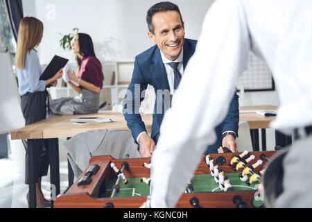 businessmen playing table football - Stock Photo