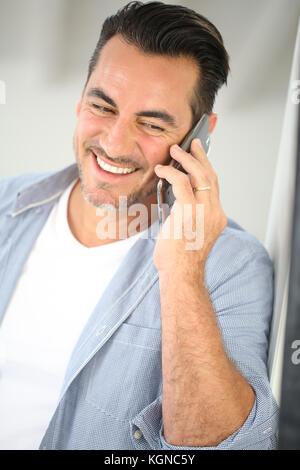 Smiling mature man talking on mobile phone - Stock Photo